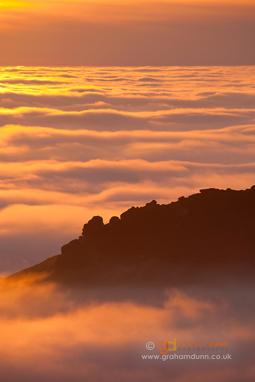 Hen Cloud emerges above the sea of golden clouds at sunset in the south-west corner of the Peak District National Park. A dramatic temperature inversion in Staffordshire, England, UK.
