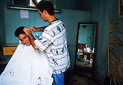 MARCH 19, 2001 - HAVANA, CUBA: A man gets a haircut in a barbershop in the barber?s home in the Regla neighborhood of Havana, Cuba, March 19, 2001. Regla is across the harbor from the rest of the city and is the center of the Santeria religion in Cuba. It is also home to many of Havana's oil refineries and heavy industries.  Many Cubans set up small businesses in their homes to supplement their state salaries.  PHOTO BY  JACK KURTZ     LABOUR  LABOR  UNEMPLOYMENT  ECONOMY