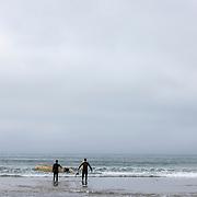 Surfers enter the water at Zuma beach in Malibu.
