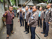 03 AUGUST 2016 - BANGKOK, THAILAND: TAWATCHAI VORAMAHAKUN, left, a community historian and leader in the Pom Mahakan slum, talks to WALLOP TANGKANA-NURAK, center, chairman of the National Legislative Assembly's (NLA) housing extraordinary committee, and other members of the NLA during a tour of the slum. Residents of the slum have been told they must leave the fort and that their community will be torn down. The community is known for fireworks, fighting cocks and bird cages. Mahakan Fort was built in 1783 during the reign of Siamese King Rama I. It was one of 14 fortresses designed to protect Bangkok from foreign invaders. Only of two are remaining, the others have been torn down. A community developed in the fort when people started building houses and moving into it during the reign of King Rama V (1868-1910). The land was expropriated by Bangkok city government in 1992, but the people living in the fort refused to move. In 2004 courts ruled against the residents and said the city could take the land. Eviction notices have been posted in the community and people given until April 30 to leave, but most residents have refused to move. Residents think Bangkok city officials will start evictions around August 15, but there has not been any official word from the city.      PHOTO BY JACK KURTZ