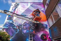 © Licensed to London News Pictures;02/04/2021; Bristol, UK. Artist Mr Cenz from London with additional work from Inkie originally from Bristol work together on a giant mural of Jen Reid, the woman who stood on the plinth of the statue of Edward Colston after it was torn down at a Black Lives Matter protest in Bristol in 2020 and of whom a statue was made and temporarily placed on the plinth. The mural is on the wall by The Canteen on Stokes Croft, and replaces an earlier mural of Breakdancing Jesus. Bristol street artist Inkie is contributing text to the mural. Photo credit: Simon Chapman/LNP.