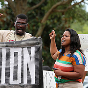 Demonstrators chant as they hold up a sign in the protest area, prior to the trial of George Zimmerman at the Seminole County Courthouse, Saturday, July 13, 2013, in Sanford, Fla. Zimmerman had been charged for the 2012 shooting death of Trayvon Martin. Zimmerman was found not guilty by a jury of six women. (AP Photo/Alex Menendez)