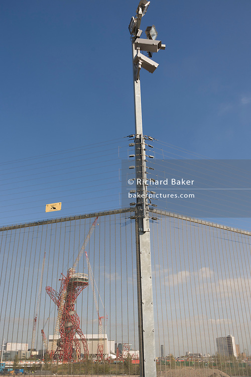CCTV cameras and The Orbit art tower seen through perimeter electrified fence at the 2012 Olympic Park site
