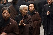 Taiwanese men ans women walk and chant quietly at Lungshan Temple in Taipei, Taiwan.