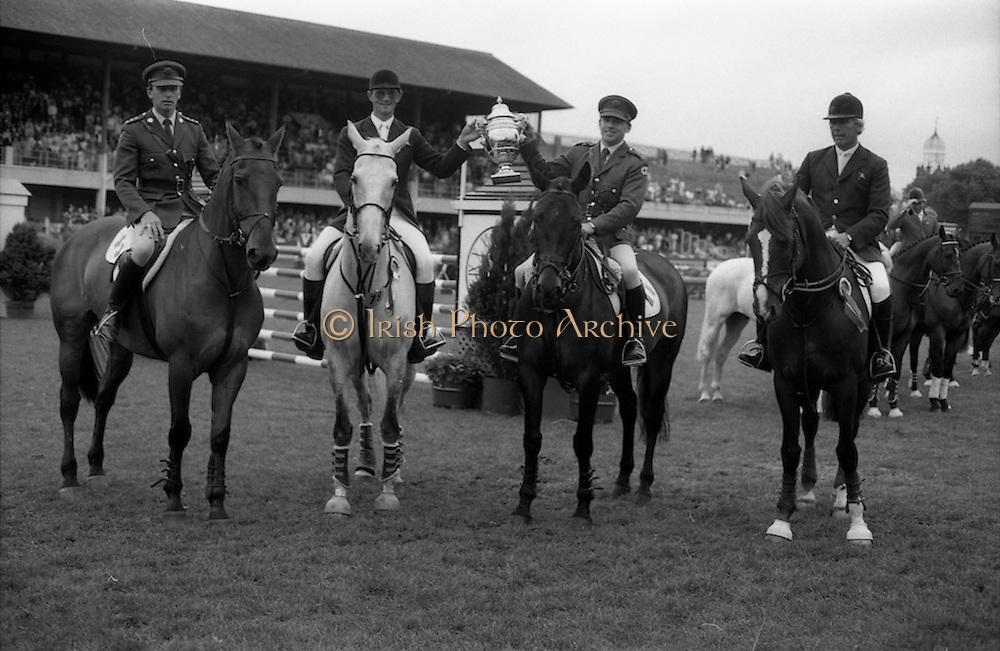 """07/08/1987<br /> 08/07/1987<br /> 07 August 1987<br /> Bank of Irelands Nations Cup for the Aga Khan trophy competition at the Dublin Horse Show at the RDS, Dublin. The winning Irish team proudly hold aloft the Aga Khan Trophy after their victory. Pictured (l-r):  Captain John Ledingham on """"Gabhran""""; Jack Doyle on """"Hardly""""; Commandant Gerry Mullins, on """"Limerick"""" and Eddie Macken on """"Carroll's Flight""""."""