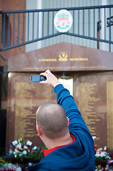 LIVERPOOL, ENGLAND - Saturday, April 11, 2009: A Liverpool supporter takes a photograph at the memorial to the 96 supporters who lost their lives at the Hillsborough Stadium Disaster on 15th April 1989. Twenty years on the victims families are still waiting for justice as none of the police officers responsible for the deaths of so many supoporters have ever been brought to justice. (Photo by: David Rawcliffe/Propaganda)