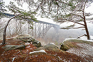 The expansive New River Gorge Bridge of West Virginia appears to nearly float in the foggy air viewed through a window of snow dusted rock and pine.