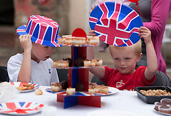 © Licensed to London News Pictures. 02/06/12. LONDON, UK. Two young boys try on a Union Jack hats as they sit with other children during a Jubilee street party held by residents of Ravenscroft Road in Canning Town, East London. The Royal Jubilee celebrations. Great Britain is celebrating the 60th  anniversary of the countries Monarch HRH Queen Elizabeth II accession to the throne this weekend Photo credit : LNP