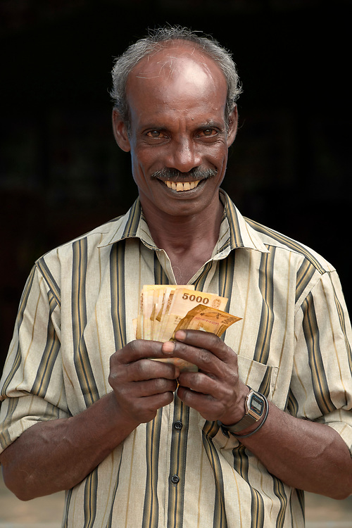 Santhosam Gnamuthu grins after getting a microcredit loan from a church group in Karadianaru, Sri Lanka. Displaced during Sri Lanka's bloody civil war, he'll use the money to buy six cows.