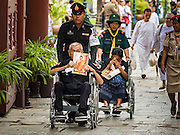 29 OCTOBER 2016 - BANGKOK, THAILAND: Thai military medic and a girl scout help people in wheelchairs go into the Grand Palace to pay homage to the late Thai King. Saturday was the first day Thais could pay homage to the funeral urn of the late Bhumibol Adulyadej, King of Thailand, at Dusit Maha Prasart Throne Hall in the Grand Palace. The Palace said 10,000 people per day would be issued free tickerts to enter the Throne Hall but by late Saturday morning more than 100,000 people were in line and the palace scrapped plans to require mourners to get the free tickets. Traditionally, Thai Kings lay in state in their urns, but King Bhumibol Adulyadej is breaking with tradition. His urn reportedly contains some of his hair, but the King is in a coffin,  not in the urn. The laying in state will continue until at least January 2017 but may be extended.       PHOTO BY JACK KURTZ