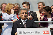 Maiaufmarsch (Labour Day March) of the SPOE (Social Democratic Party of Austria). Leading SPOE politicians holding speeches at the Rathaus (City Hall), here Austrian Chancellor Werner Faymann.  Chatting behind: Doris Bures, Minister of Infrastructure (l.) and Viennese City Counselor Sonja Wehsely (r.)