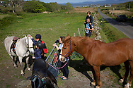 Local GP Jan Brooks (second left) giving a riding lesson to an islander on the the Inner Hebridean island of Colonsay on Scotland's west coast.  The island is in the council area of Argyll and Bute and has an area of 4,074 hectares (15.7 sq mi). Aligned on a south-west to north-east axis, it measures 8 miles (13 km) in length and reaches 3 miles (4.8 km) at its widest point, in 2019 it had a permanent population of 136 adults and children.