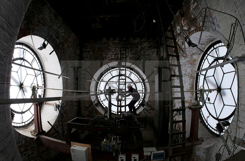 © Licensed to London News Pictures. 08/10/2018. Wakefield, Leeds. A contractor makes final checks to the clock mechanism, inside Wakefield Town Hall Clock Tower, ahead of British Summer Time coming to an end. Clocks are set back one hour at 2am on Sunday, 28 October. Picture Scott Merrylees/LNP