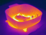 Thermogram of a hot dish of food.  The different colors represent different temperatures on the object. The lightest colors are the hottest temperatures, while the darker colors represent a cooler temperature.  Thermography uses special cameras that can detect light in the far-infrared range of the electromagnetic spectrum (900?14,000 nanometers or 0.9?14 µm) and creates an  image of the objects temperature..