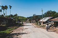 Kalaw, Myanmar - October 31, 2011: People walk on the side of the main highway in a small settlement near the town of Kalaw.