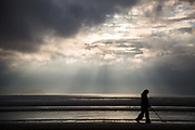 A woman seach for treasure with a metal detector at sunset in the sea side town Weston Super-Mare.