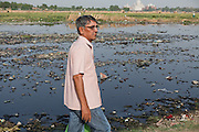 Brij Khandelwal, a renown environmental journalist for the Times of India, is walking on a bank of the heavily polluted Yamuna River, in Agra, opposite the Taj Mahal complex.