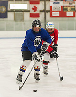 Leslie Hoyt Blue team and Nancy Voorhis Red team go for the puck during the Lakes Region Womens Hockey Club game on Tuesday evening.  (Karen Bobotas/for the Laconia Daily Sun)