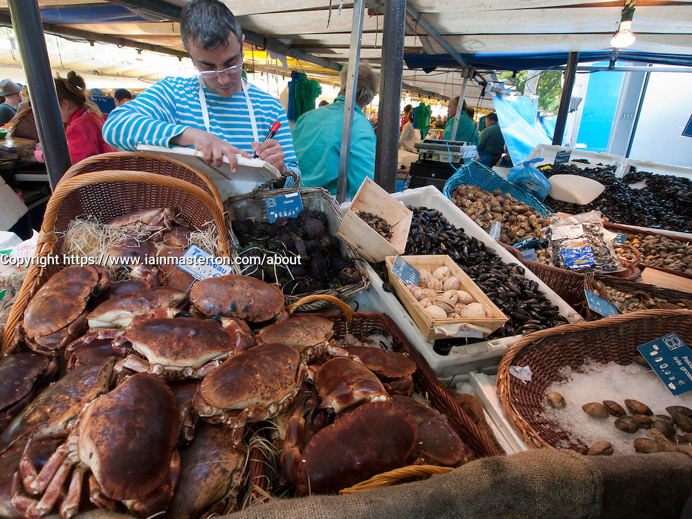 Crabs and shellfish for sale at traditional market at Bastille in Paris France