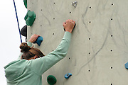 Young teen girl climbs up an artificial climbing wall close up of the hands
