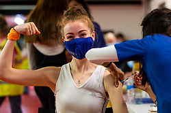 """© Licensed to London News Pictures. 27/06/2021. WATFORD, UK. Imogen Noore (aged 21) receives a first dose of the Pfizer vaccine at a pop-up mass vaccination clinic at Watford FC's Vicarage Road Stadium as part of the """"Grab a jab"""" campaign. The NHS is also promoting a number of walk-in clinics this weekend across the capital to try to increase the number of over 18s receiving a jab as cases of the Delta variant are reported to be on the rise..  Photo credit: Stephen Chung/LNP"""