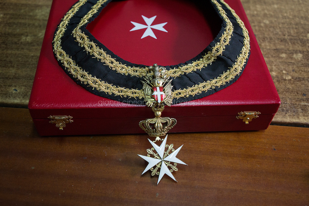 """VALLETTA, MALTA - 2 November 2013: The eight-pointed Maltese Cross belonging to Marquis Nicholas de Piro (72), a Knight Hospitaller of the Order of St. John of Jerusalem (also known as Knights of Malta), is here in his studio at Casa Rocca Piccola, a 16th-century palace and home of the noble de Piro family in Valletta, Malta, on November 2nd 2013. <br /> <br /> Casa Rocca Piccola was one of two houses built in Valletta by Admiral Don Pietro la Rocca. It is referenced in maps of the time as """"la casa con giardino"""" meaning, the house with the garden, as normally houses in Valletta were not allowed gardens.<br /> <br /> Valleta was named after Jean Parisot de Valette of the Order of St. John of Jerusalem, who succeeded in defending the island from an Ottoman invasion in 1565, known as the Siege of Malta. The city was founded immediately after the end of the Siege of Malta to fortify the Order's position in Malta and bind the Knights to the island."""