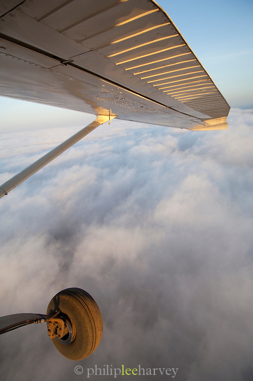 View of airplane wing above the clouds of Chyulu Hills, Kenya