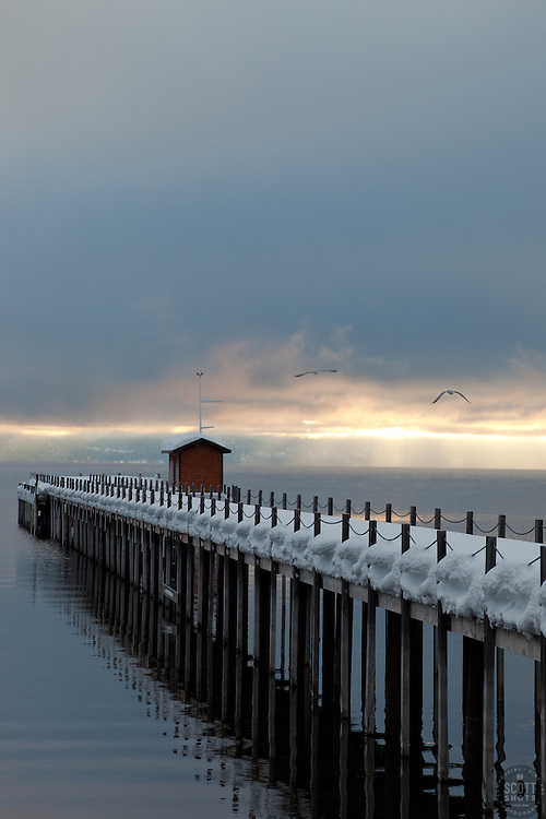 """""""Snowy Pier in Tahoe City 1""""- This snow covered pier and two flying birds were photographed in the early morning near Commons Beach in Tahoe City, CA."""