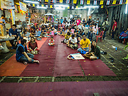 25 SEPTEMBER 2016 - BANGKOK, THAILAND: Residents of the Pom Mahakan community wait for the show to start before a Likay performance in Pom Mahakan Fort. The performance was to support residents of the old fort, who are fighting eviction orders by the city of Bangkok. City officials have made repeated attempts to evict people since Sept 3, 2016, but about 44 families are still living in the community. Likay is a form of popular folk theatre from Thailand. It uses a combination of extravagant costumes, barely equipped stages and vague storylines. The performances depend mainly on the actors' skills of improvisation and the audiences' imagination. There used to be several Likay troupes based in the old fort, but they left the community more than 50 years ago. The troupe that performed Sunday night was an amateur troupe comprised of college students and office workers.      PHOTO BY JACK KURTZ