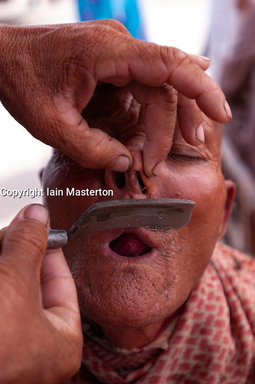 Uyghur man having a shave at Kashgar Sunday Market in Xinjiang, China