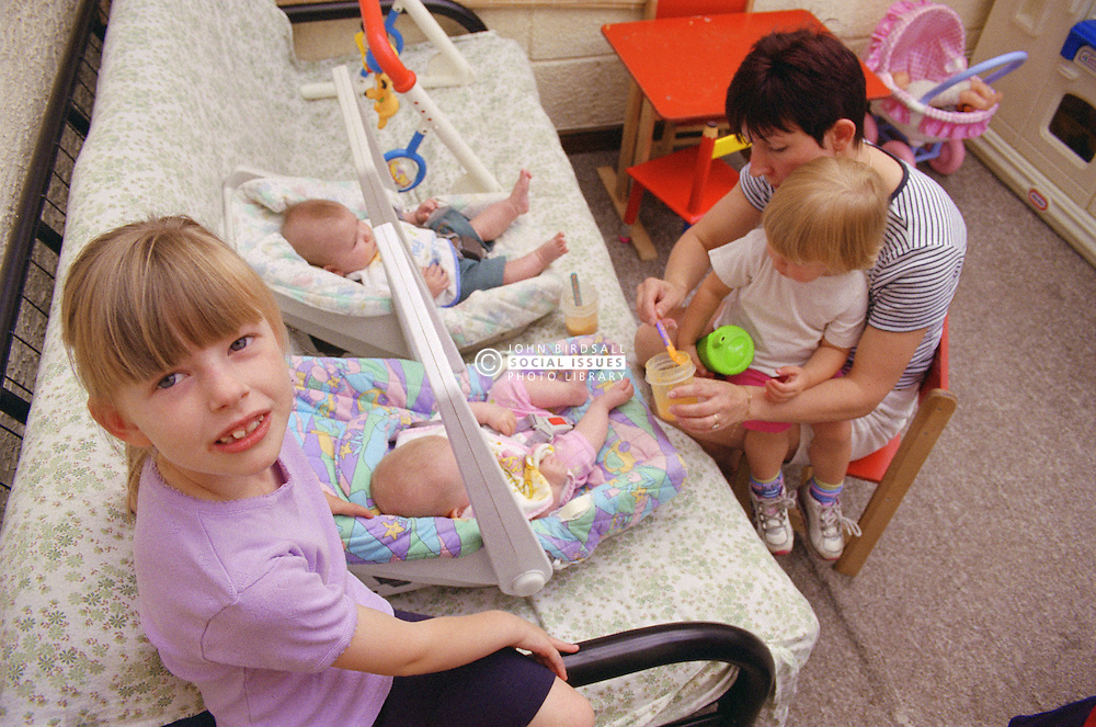 Mother feeding twin babies with older sisters watching,