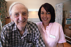 Health care worker and elderly patient standing together smiling,