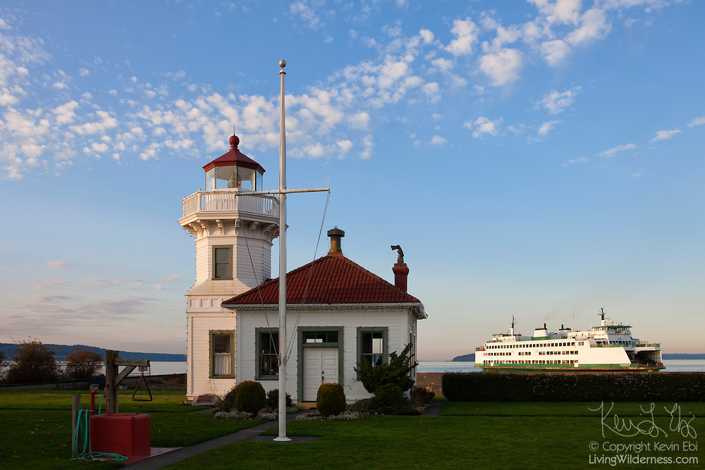 A Washington State ferry passes by the Mukilteo Light, a lighthouse that began operating in 1906 in Mukilteo, Washington. The lighthouse, one of the few made out of wood, was placed on the National Register of Historic Places in 1977 and automated two years later. The lighthouse is now maintained by the Mukilteo Historical Society.
