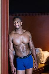 muscular black man in his underwear standing in a bedroom doorway