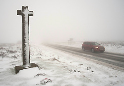 © Licensed to London News Pictures. 27/01/2014 North York Moors, England A motorist drives past Ralph's Cross following another night of snow on the North York Moors.<br /> Photo credit : Ian Forsyth/LNP