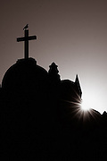 The setting sun peeks from behind this church in Tucson, Arizona.