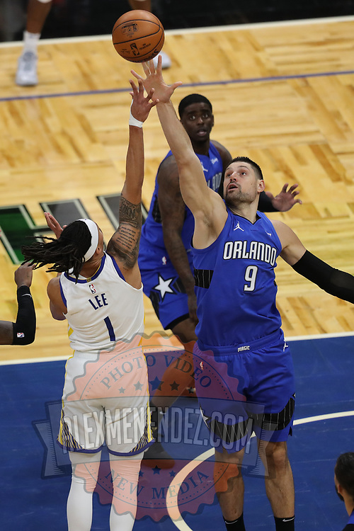 ORLANDO, FL - FEBRUARY 19:  Nikola Vucevic #9 of the Orlando Magic leaps against Damion Lee #1 of the Golden State Warriors during the first half at Amway Center on February 19, 2021 in Orlando, Florida. NOTE TO USER: User expressly acknowledges and agrees that, by downloading and or using this photograph, User is consenting to the terms and conditions of the Getty Images License Agreement. (Photo by Alex Menendez/Getty Images)*** Local Caption *** Nikola Vucevic ;Damion Lee