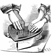 Planchette or Ouija board, 1885. Method of using the Planchette for spirit writing during a séance.  From 'The Scientific American' (New York, 1885). Wood engraving.