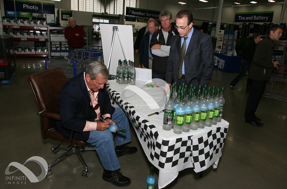 Fuzzy Zoeller signs bottles of Fuzzy's Ultra Premium Vodka at Sam's Club in Indianapolis, Indiana.