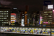 People and a Chuo Soba line train at night at Iidabashi station , Tokyo, Japan. Tuesday December 3rd 2019