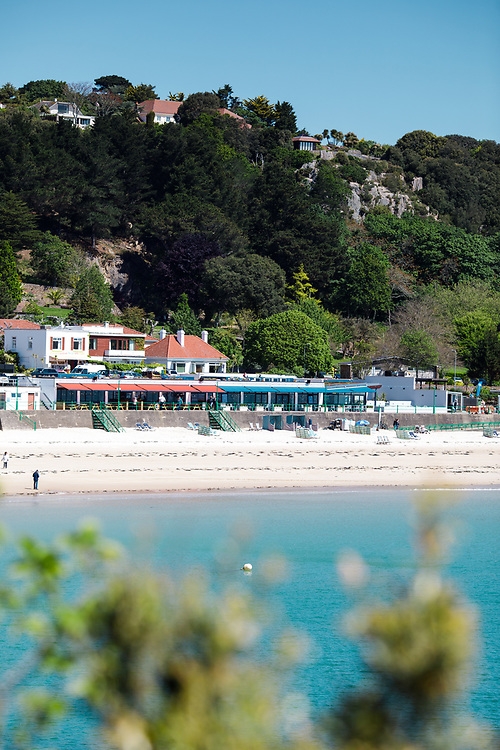 Beachfront restaurants overlooking the white sand and turquoise water on the beach at St Brelade, a popular tourist destination in Jersey, Channel Islands
