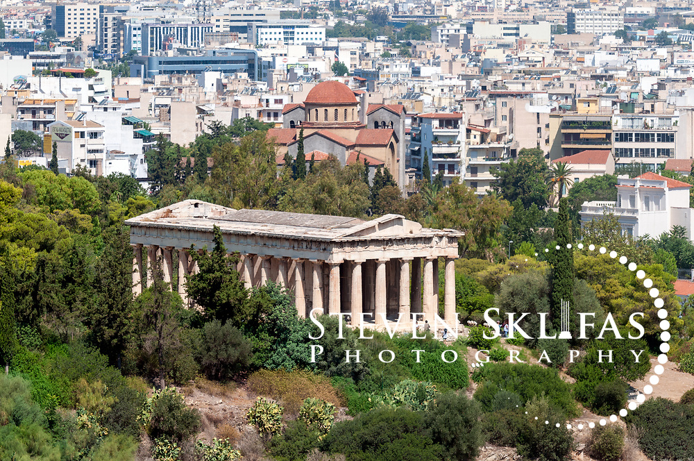 Ancient Agora. Athens. Greece. View of the Hephaisteion, the Temple dedicated to Hephaestus and Athena, divinities of metalworkers and artisans. The Temple which crowns the Agoraios Kolonos hill overlooking the Agora was built between 450-415 BC; the build time was protracted as it was competing for workers due to the great period of rebuilding after the Persians wars. The temple, which is the best preserved of antiquity, has a marble Doric peristyle of 36 columns (6 by 13 columns) and is smaller than the majestic Parthenon although it shares the masterful optical refinements of the famous landmark.
