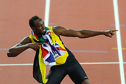 London, 2017 August 05. Usain Bolt bows out of competitive athletics with his trademark pose, draped in the Jamaican and British flags at the IAAF World Championships London 2017. © Paul Davey.