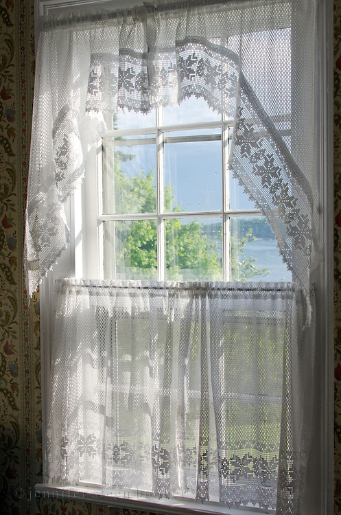 Looking through a lace-curtained window to green trees and blue ocean