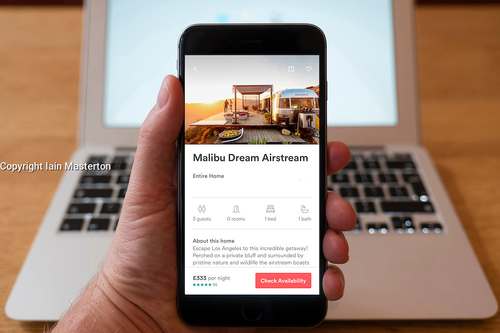 Using iPhone smartphone to display logo of Airbnb app with vintage luxury Airstream caravan in Malibu California