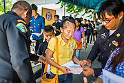 "17 JULY 2014 - BANGKOK, THAILAND: Thai immigration police check the temporary ID cards of undocumented Cambodian workers at the temporary ""one stop service center"" in the Bangkok Youth Center in central Bangkok. Thai immigration officials have opened several temporary ""one stop service centers"" in Bangkok to register undocumented immigrants and issue them temporary ID cards and work permits. The temporary centers will be open until August 14.    PHOTO BY JACK KURTZ"