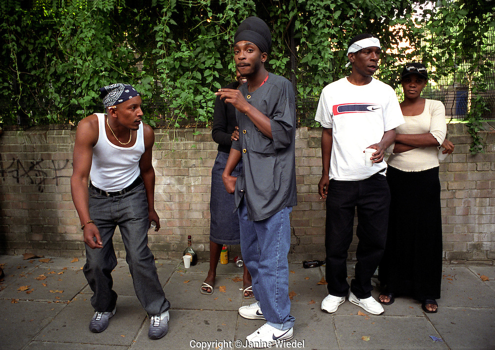 Group of young Asian Afro Caribbean men fooling around in the street.