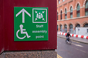 A green emergency evacuation assembly meeting point for staff outside the British Library in London, United Kingdom.  The sign also shows the international symbol of access signposting people to the disability meeting point.