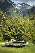 Side view of hiker lying on a bench in a natural setting, Routeburn Shelter, South Island, New Zealand