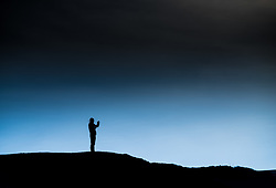 The silhouette of a man seen in early morning winter light.